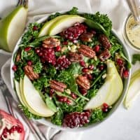 bowl of pear salad with fresh pomegranates and candied pecans and orange poppyseed dressing jar
