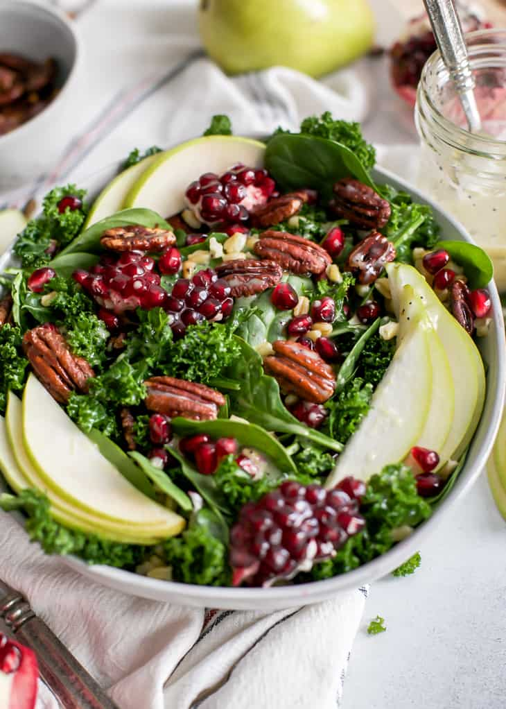 pear salad with pomegranates and candied pecans in serving bowl