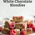 plate of raspberry white chocolate blondies piled up with raspberries