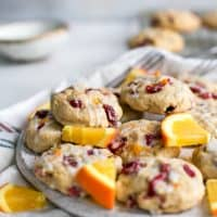 plate of cranberry orange cookies with orange slices