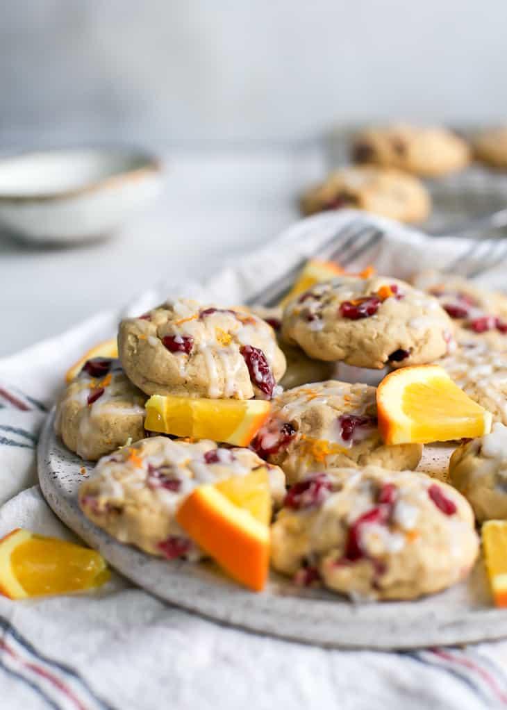 plate of cranberry orange cookies with orange slices