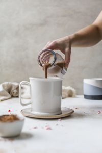 peppermint mocha coffee creamer in clear bottle with white coffee mugs