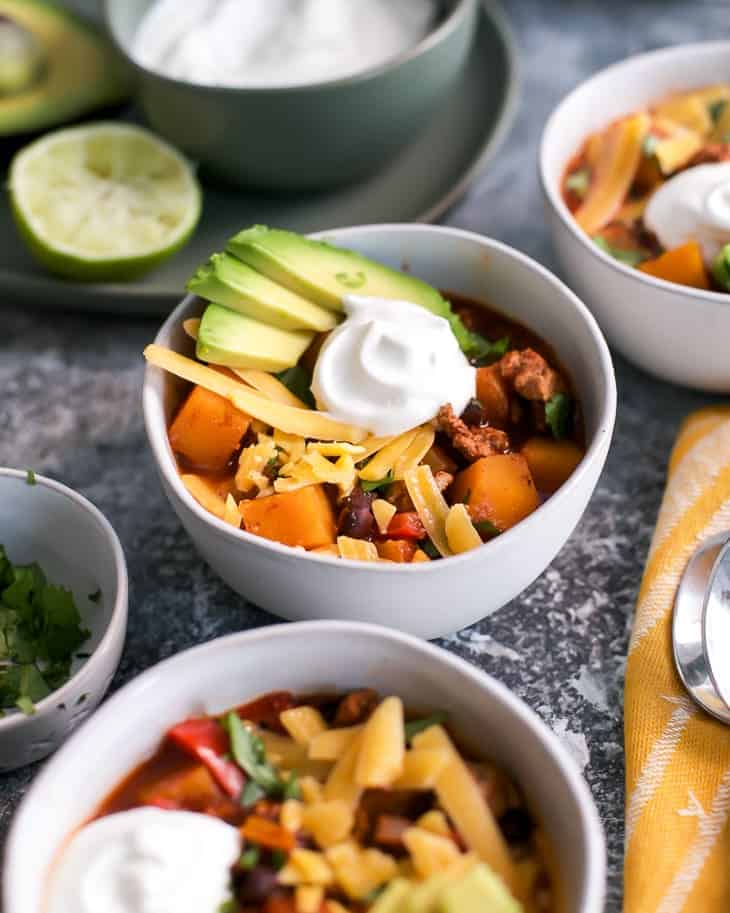 avocado, sour cream and cheese topped turkey chili bowls