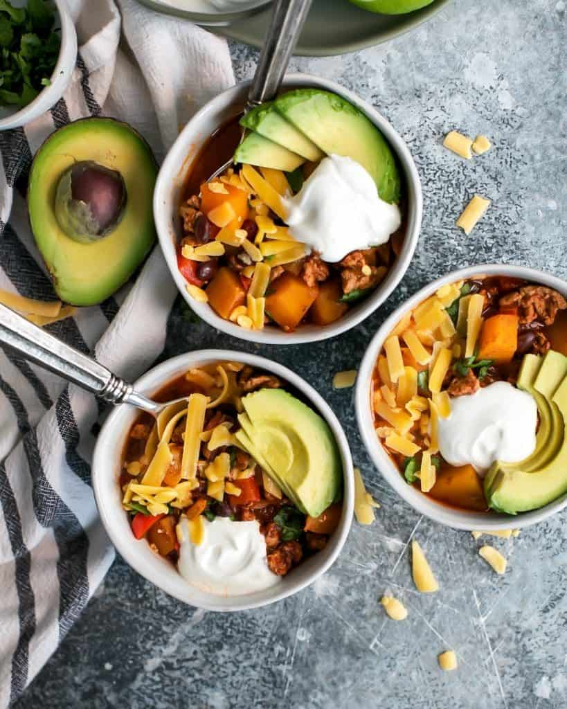 white bowls with chili topped with cheese avocado and sour cream