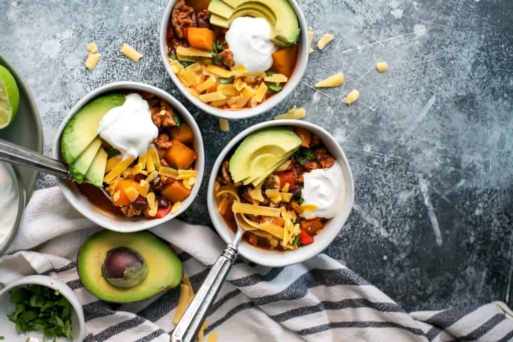 three bowls turkey chili topped with avocado, sour cream and cheddar cheese