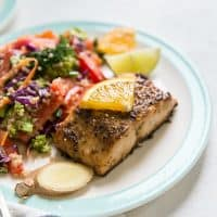 ginger salmon with orange slice with asian quinoa salad on plate