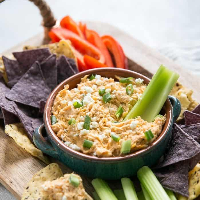 buffalo chicken dip with celery and chips on tray