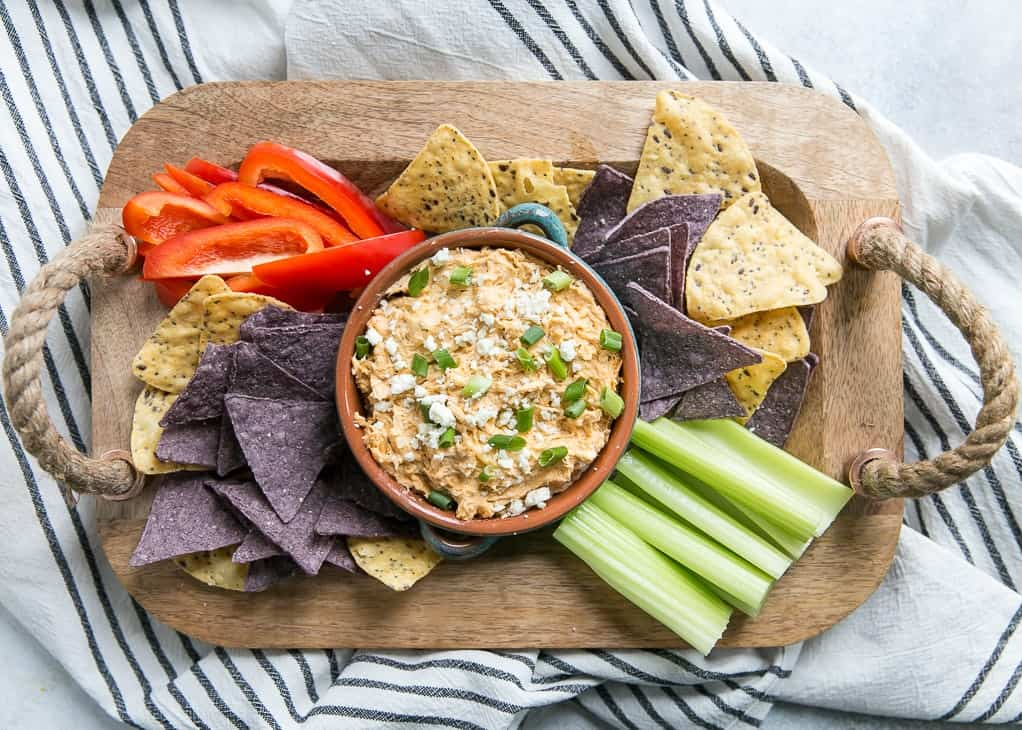 buffalo chicken dip on tray with chips, peppers and celery