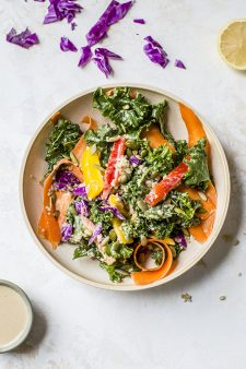 rainbow kale quinoa salad on plate with lemon and dressing