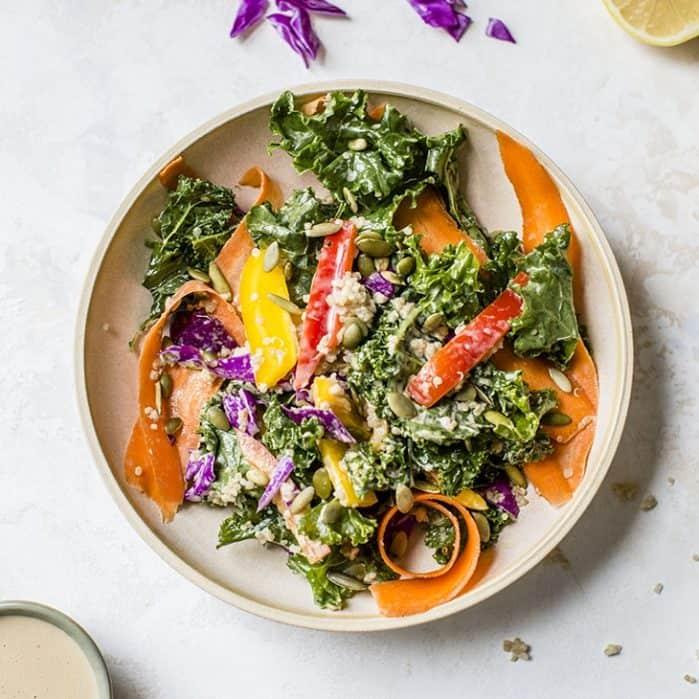rainbow kale quinoa salad on plate with lemon and dressing