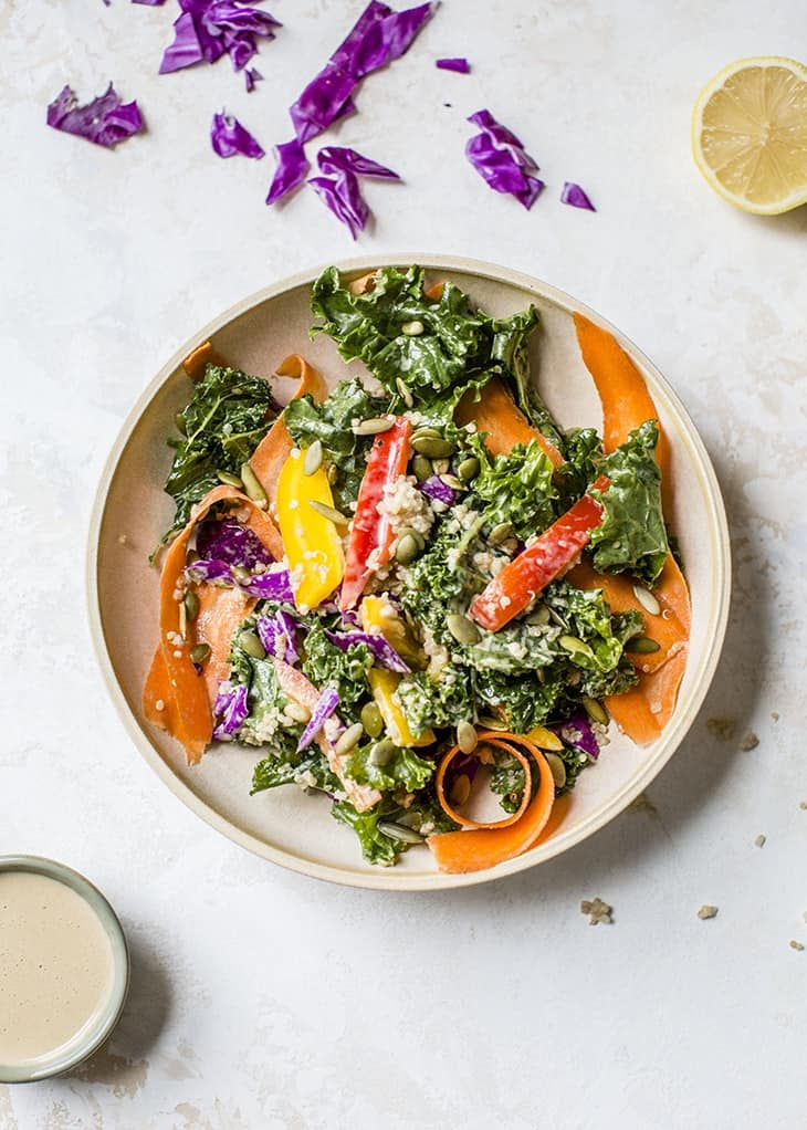 rainbow kale quinoa salad on plate with lemon and ginger dressing