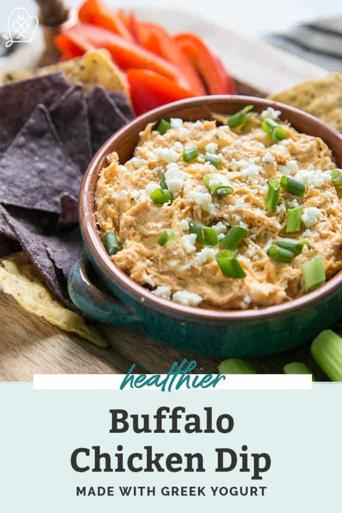 buffalo chicken dip in small bowl surrounded by chips and veggies