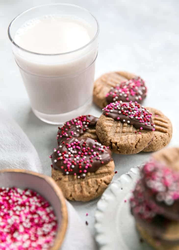 sprinkles chocolate dipped cookies with glass of milk