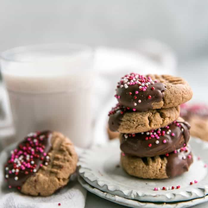 stack of chocolate dipped cashew butter cookies on plates with glass of milk