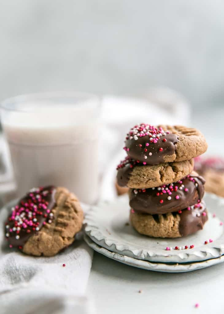 stacked chocolate dipped cashew butter cookies on plate with milk