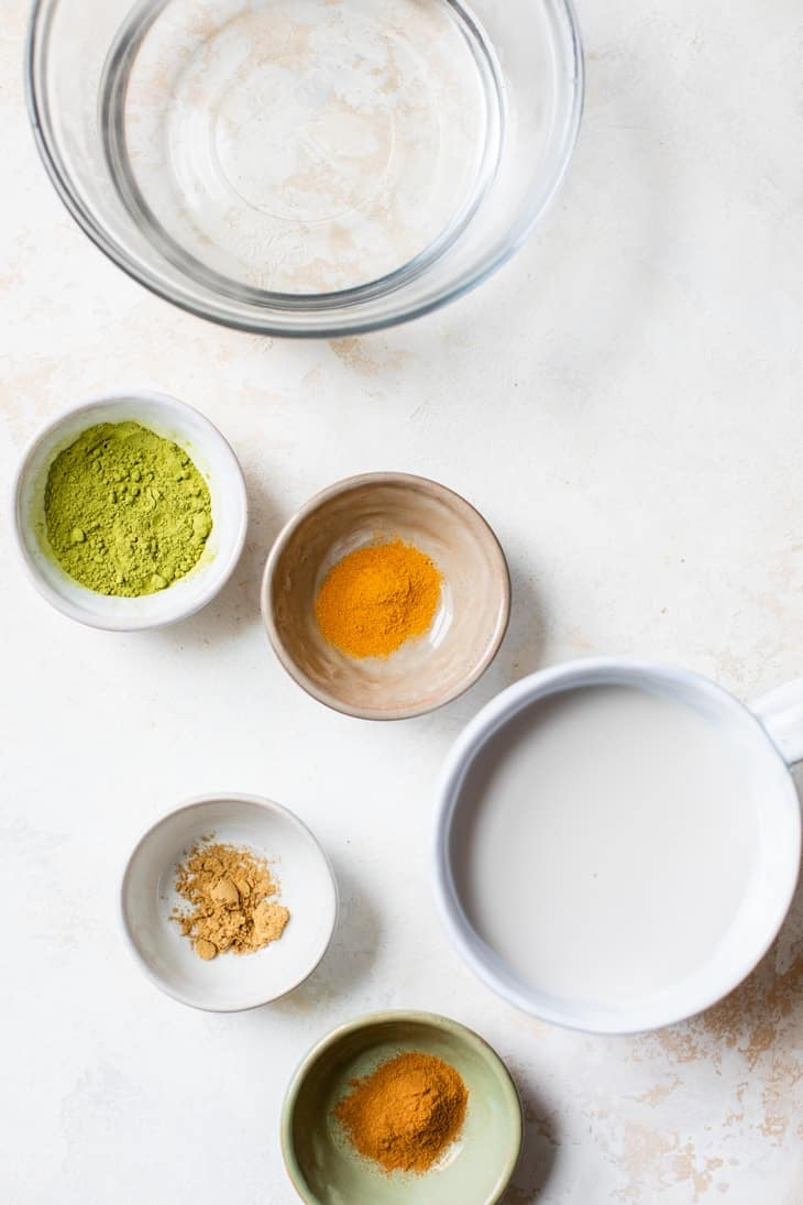 ingredients for spiced matcha latte in white bowls