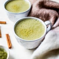 spiced matcha latte in white mugs with cinnamon sticks and towel