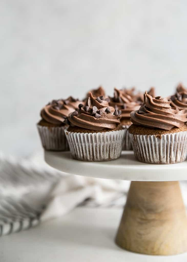 chocolate frosted cookie dough cupcakes on marble cake stand