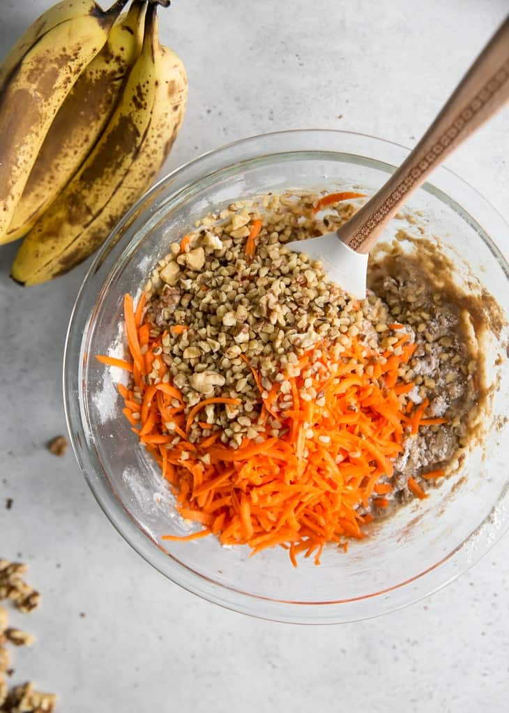 mixing bowl of carrot cake banana bread batter with walnuts
