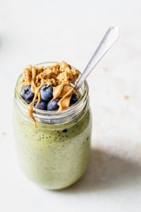 matcha overnight oats in jar with blueberries and toppings