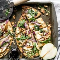 pear flatbread on sheet pan with pizza cutter