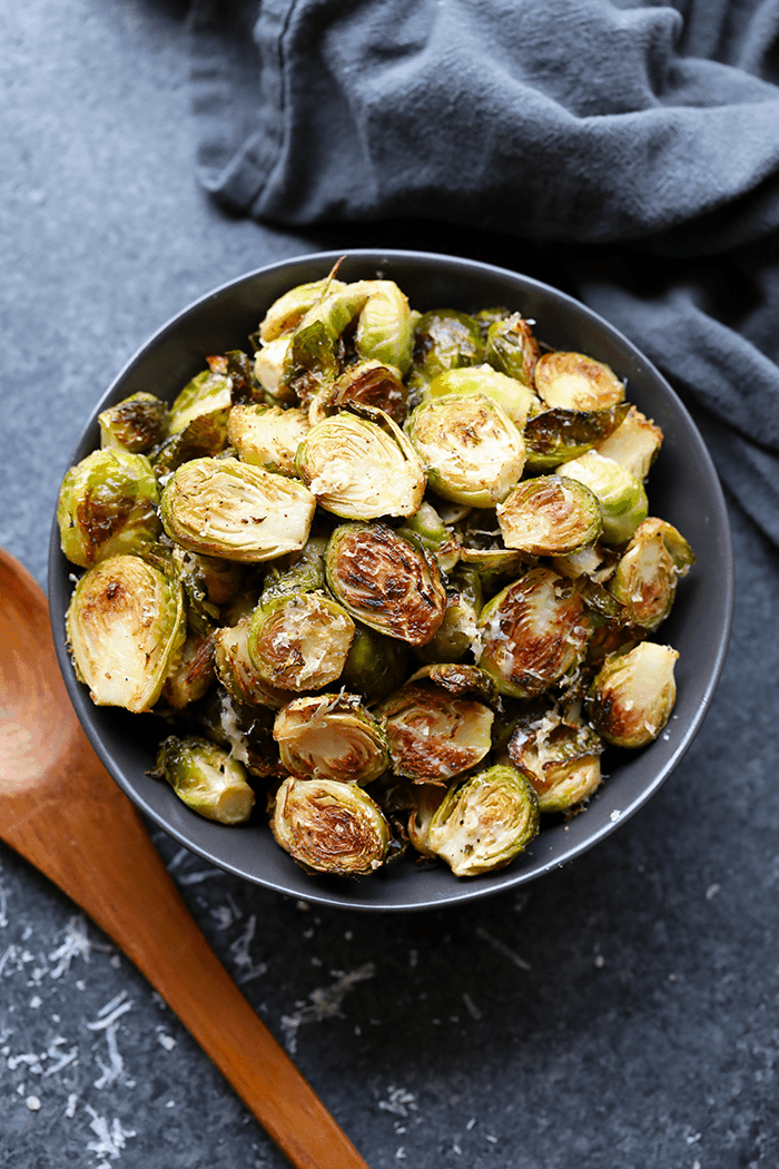 brussels sprouts in gray bowl with parmesan cheese and wooden spoon