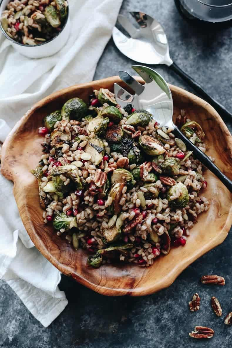 brussels sprouts farro salad in wooden bowl with silver serving spoons