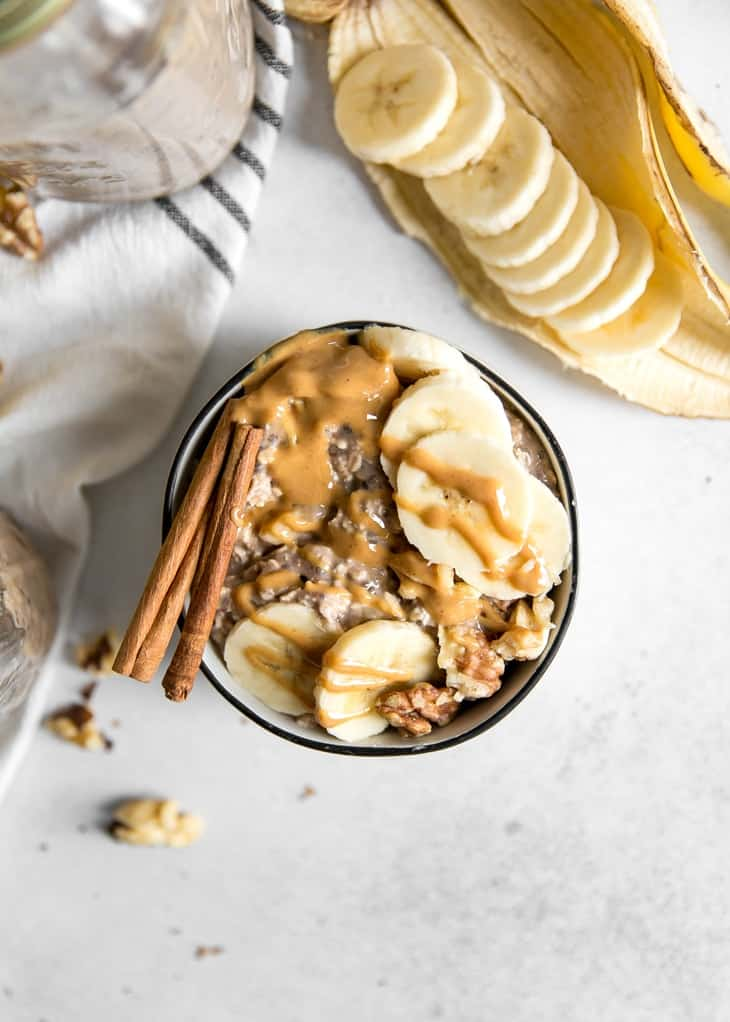 overnight oats in bowl with banana slices and peanut butter