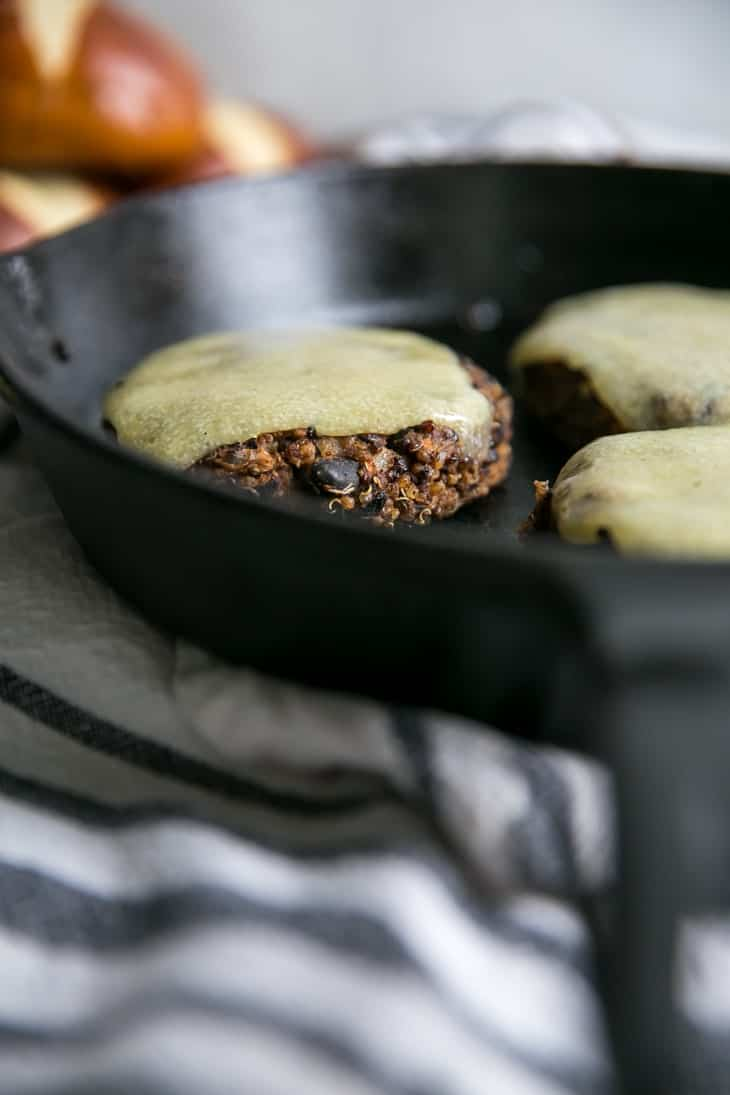 cheese melted on quinoa black bean burgers in pan