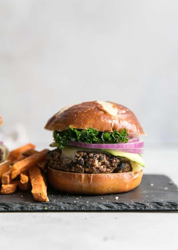 quinoa black bean burger patty on but with sweet potato fries on slate