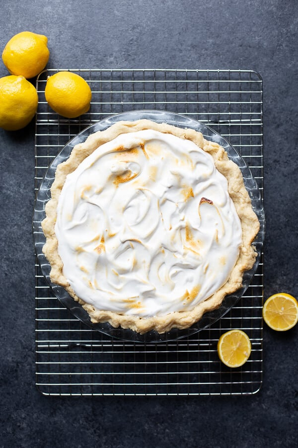meringue pie on a cooling rack surrounded by lemons