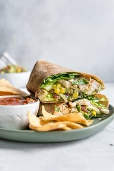 Southwest chicken wrap on green plate with chips and salsa