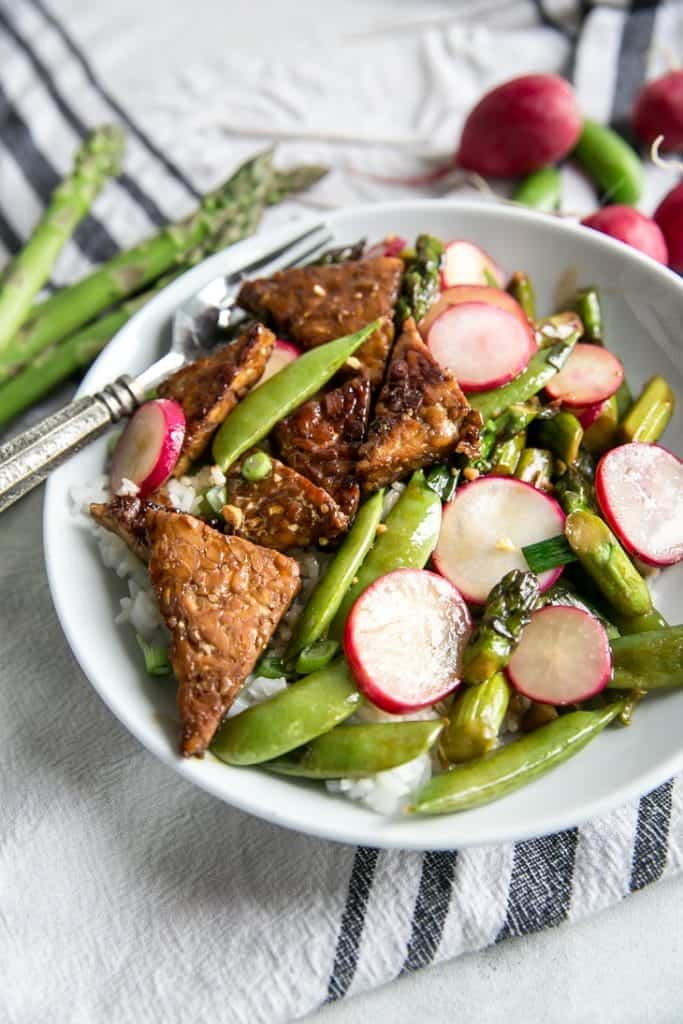 vegetable stir fry in bowl with radishes & sugar snap peas