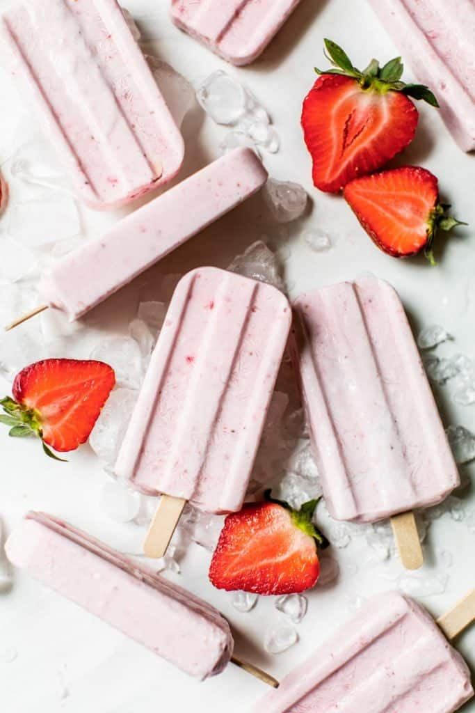 strawberry popsicles on board with ice and fresh strawberries