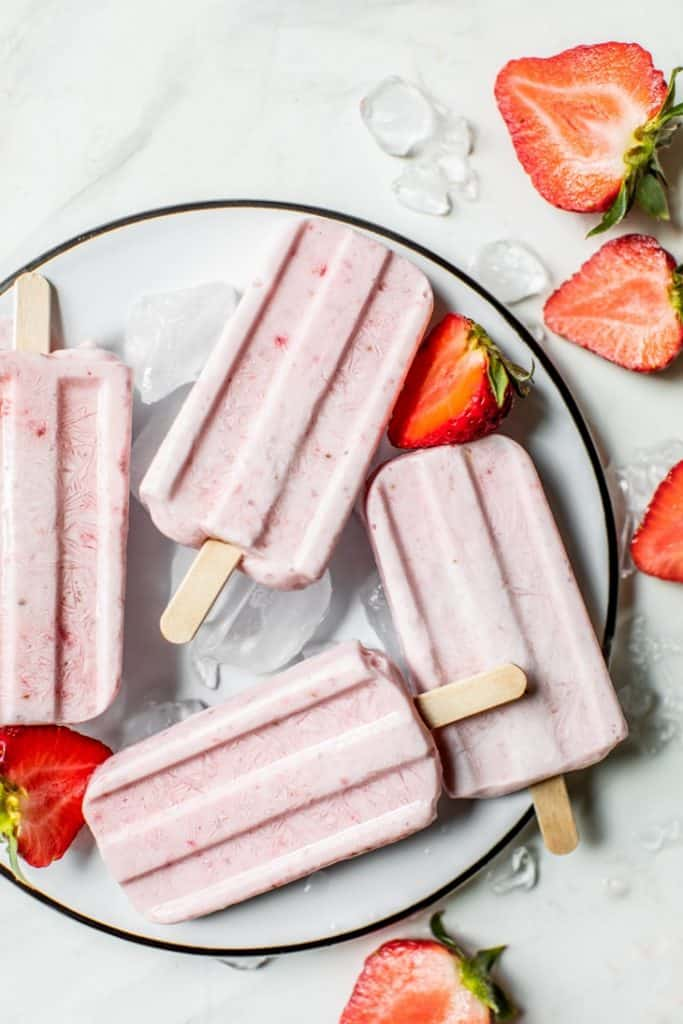 strawberry popsicles on black rimmed plate with ice and fresh strawberries