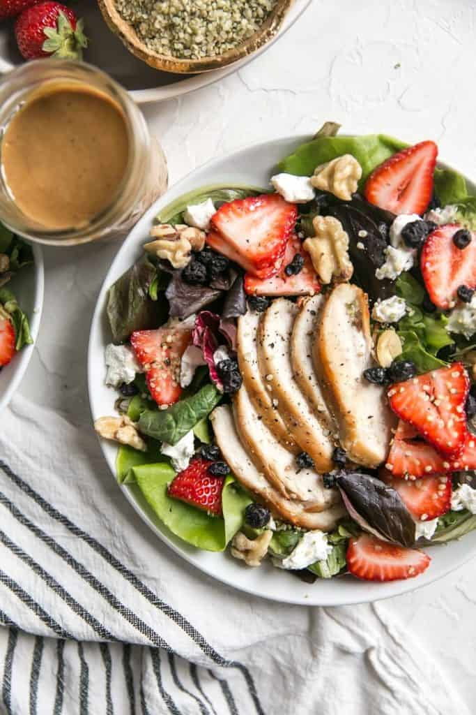 grilled chicken strawberry salad in a white bowl with almond butter dressing