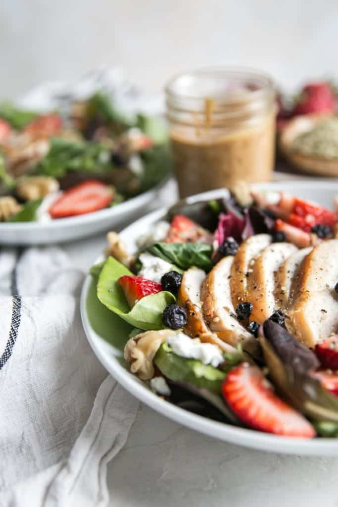 strawberry salad with grilled chicken in two white bowls with almond butter dressing