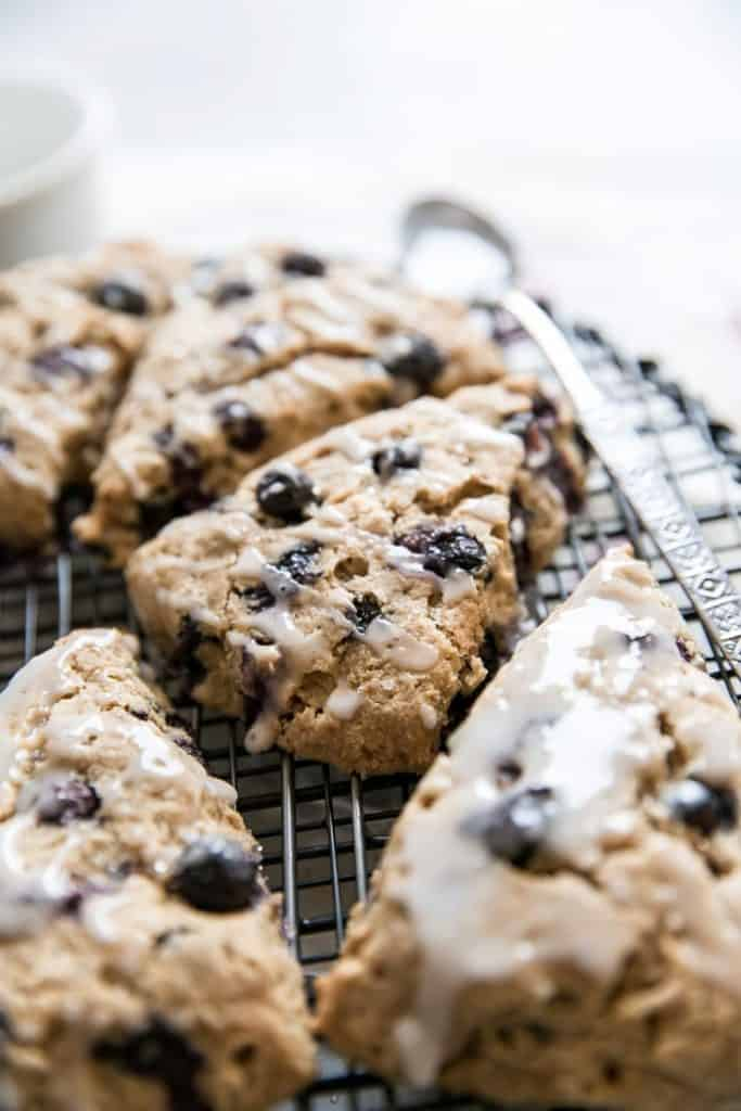 glazed blueberry scones on cooling rack with spoon