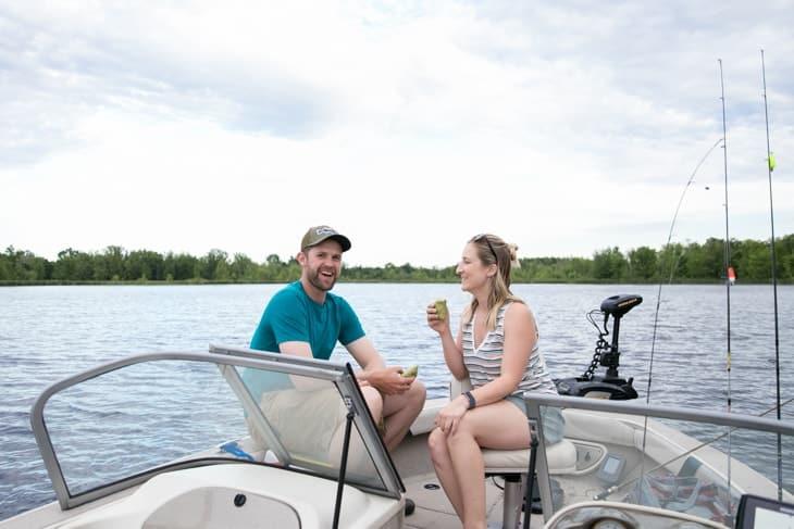 couple on boat enjoying wrap lunch