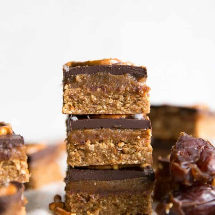 caramel pretzel bars with dried dates on parchment paper