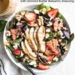 grilled chicken strawberry salad in a white bowl with a fork