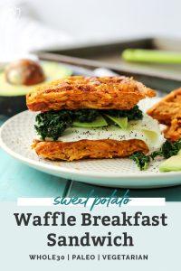 a paleo sweet potato waffle breakfast sandwich with kale, avocado and fried egg on white plate on turquoise board