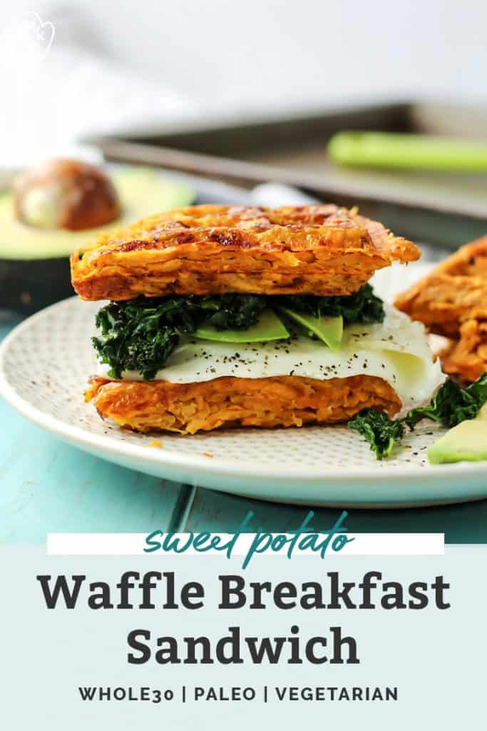 a paleo sweet potato waffle breakfast sandwich with kale, avocado and fried egg on white plate on turquoise board