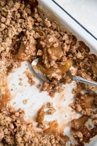 spoon in pan of baked apple crisp