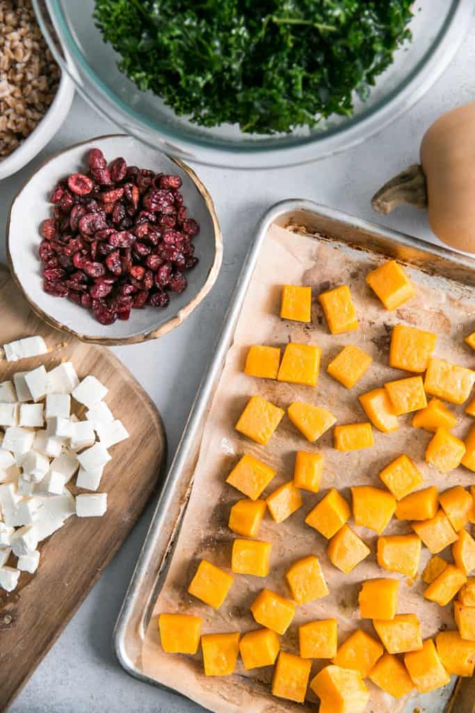 roasted butternut squash in pan, feta and dried cranberries in bowl