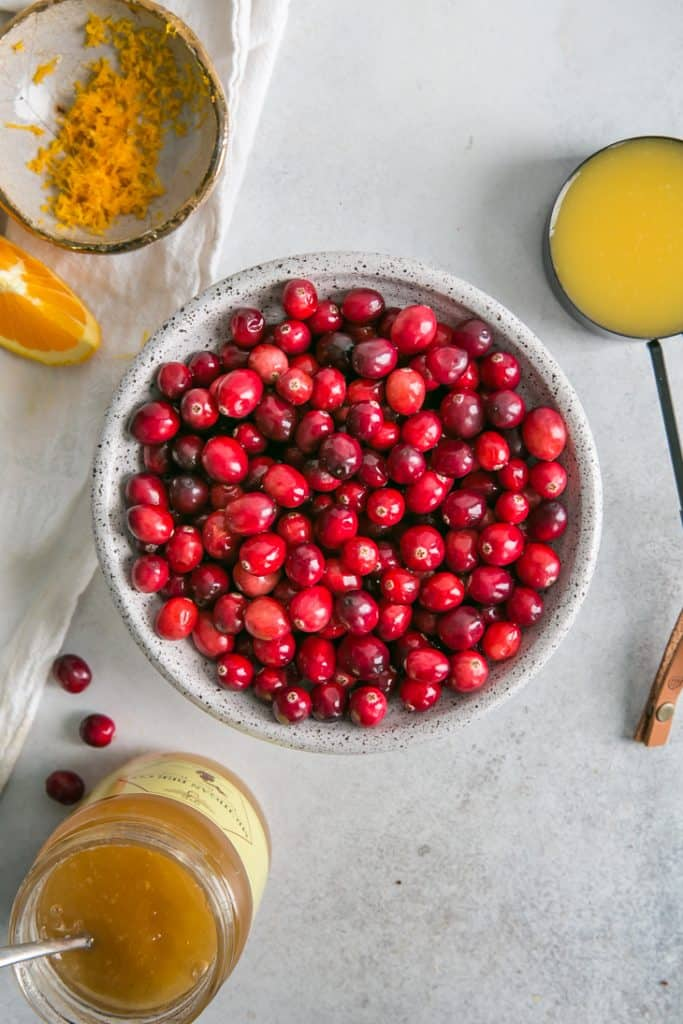 cranberries in bowl with honey, orange juice