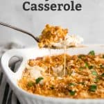 spoon lifting cheesy potatoes out of casserole dish