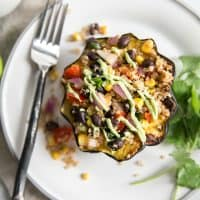 stuffed acorn squash on plate with cilantro and fork