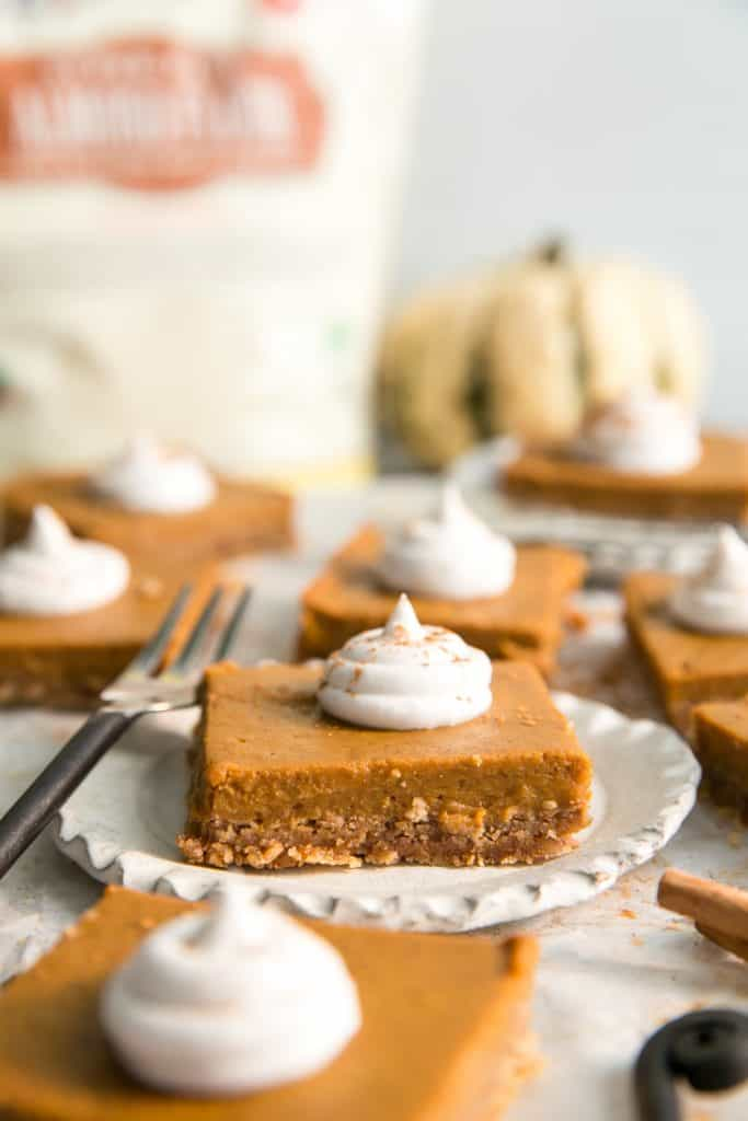 paleo pumpkin pie bars on small plate with whipped dollop
