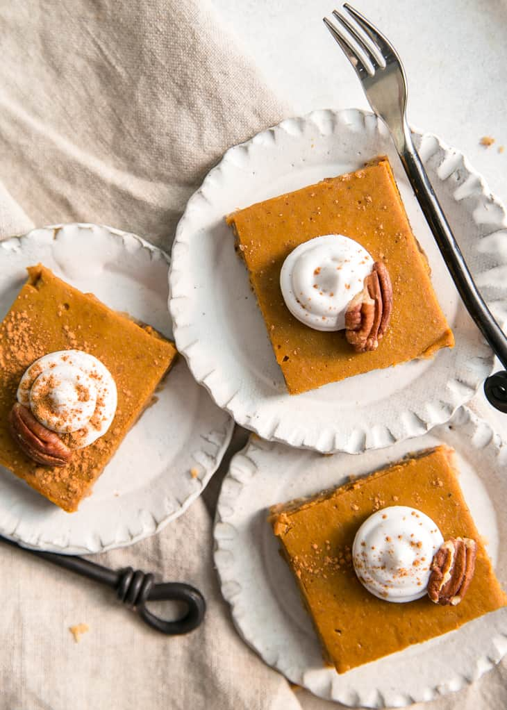 pumpkin pie bars on little plates with whipped cream and pecans